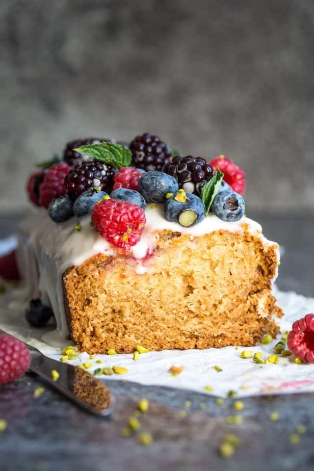 Vegan lemon and raspberry loaf cake, topped with raspberries, blackberries, and blueberries.